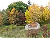 Havenwoods State Forest entrance sign surrounded by bright yellow and deep red fall foliage.
