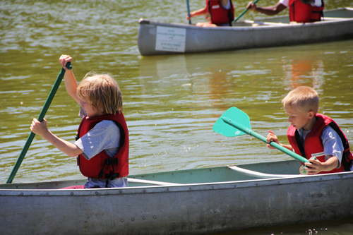 Boys paddling in a canoe in the Washington Park lagoon