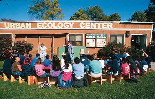 Students sitting outside our original Urban Ecology Center building -- a double wide trailer