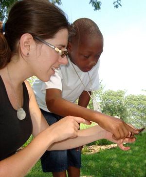 Teacher and student carefully check out a Monarch Butterfly