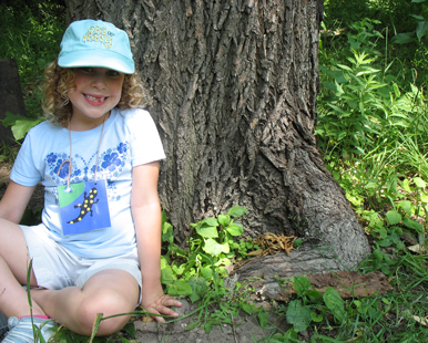 Smiling, curlyhaired girl sitting by the base of a tree