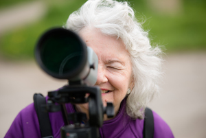 Woman looking at camera through a spotting scope.