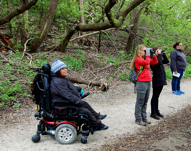 A woman in a power chair, two women looking through binoculars all on a pressed limestone path