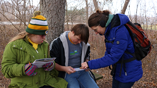 Two students and an education examine a piece of wood, comparing it to their chart.