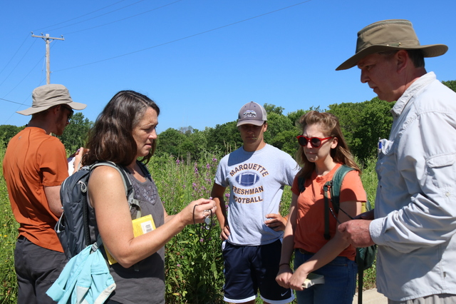 Kim Forbeck, Manager of Land Stewardship, is explaining a plant that she is holding to a group of adults.