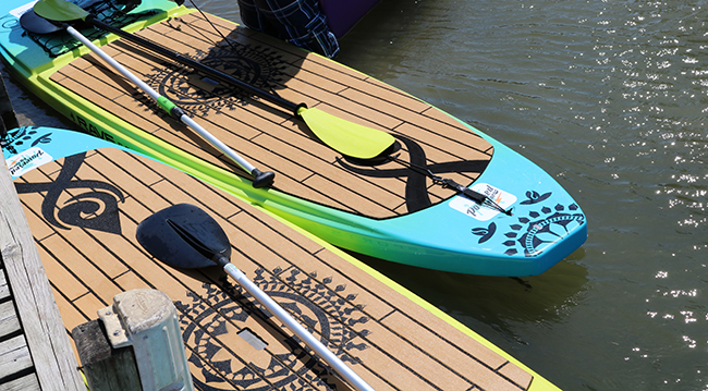 Two brightly colored paddle boards next to a dock on a lake