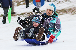 A kid and adult sledding