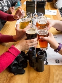 Hands clinking glasses of beer over two sets of binoculars