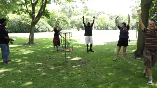 A group of friends playing disc golf in the park